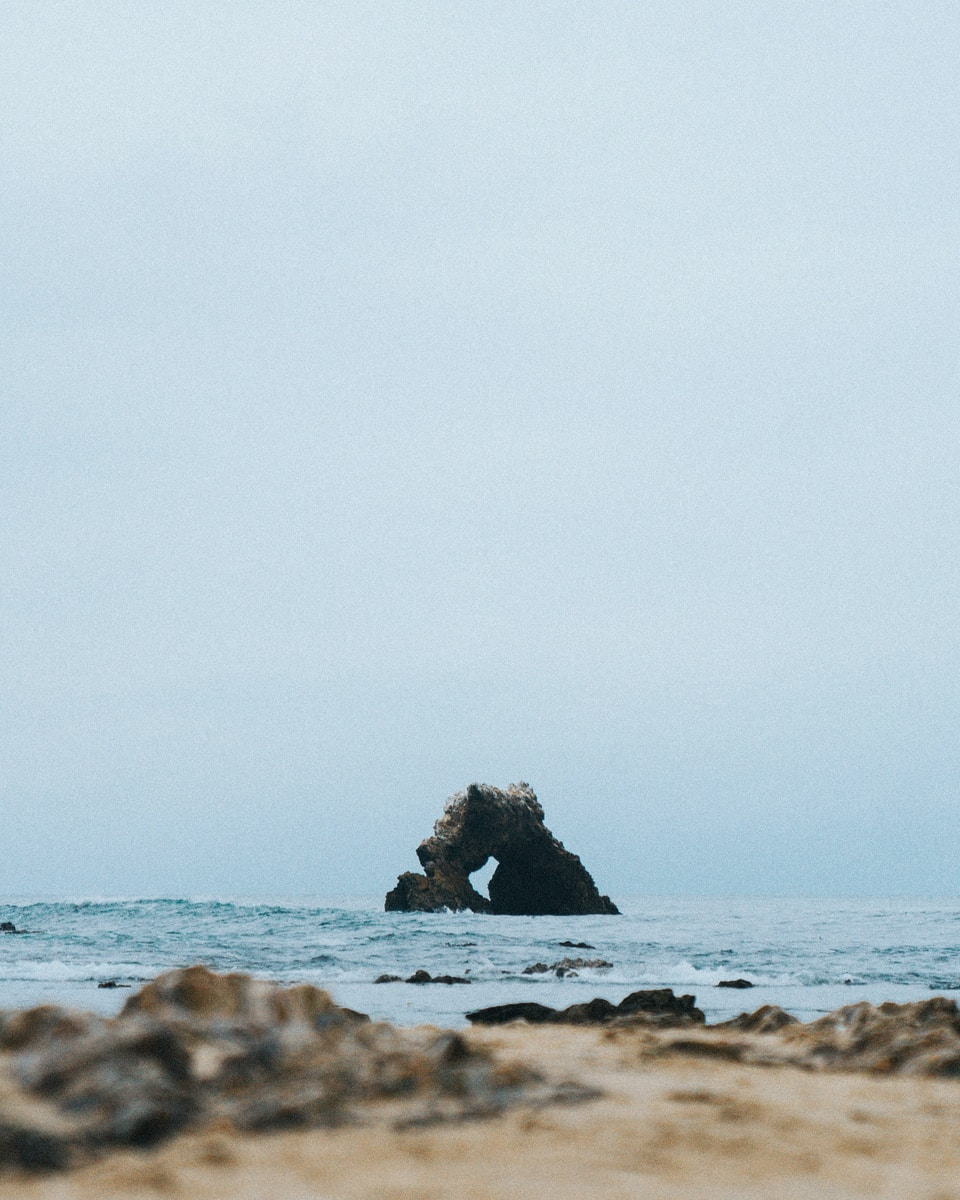 selective focus photography of rock monolith at the middle of the sea