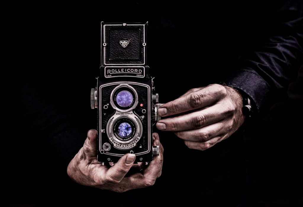 person holding black twin lens reflex camera