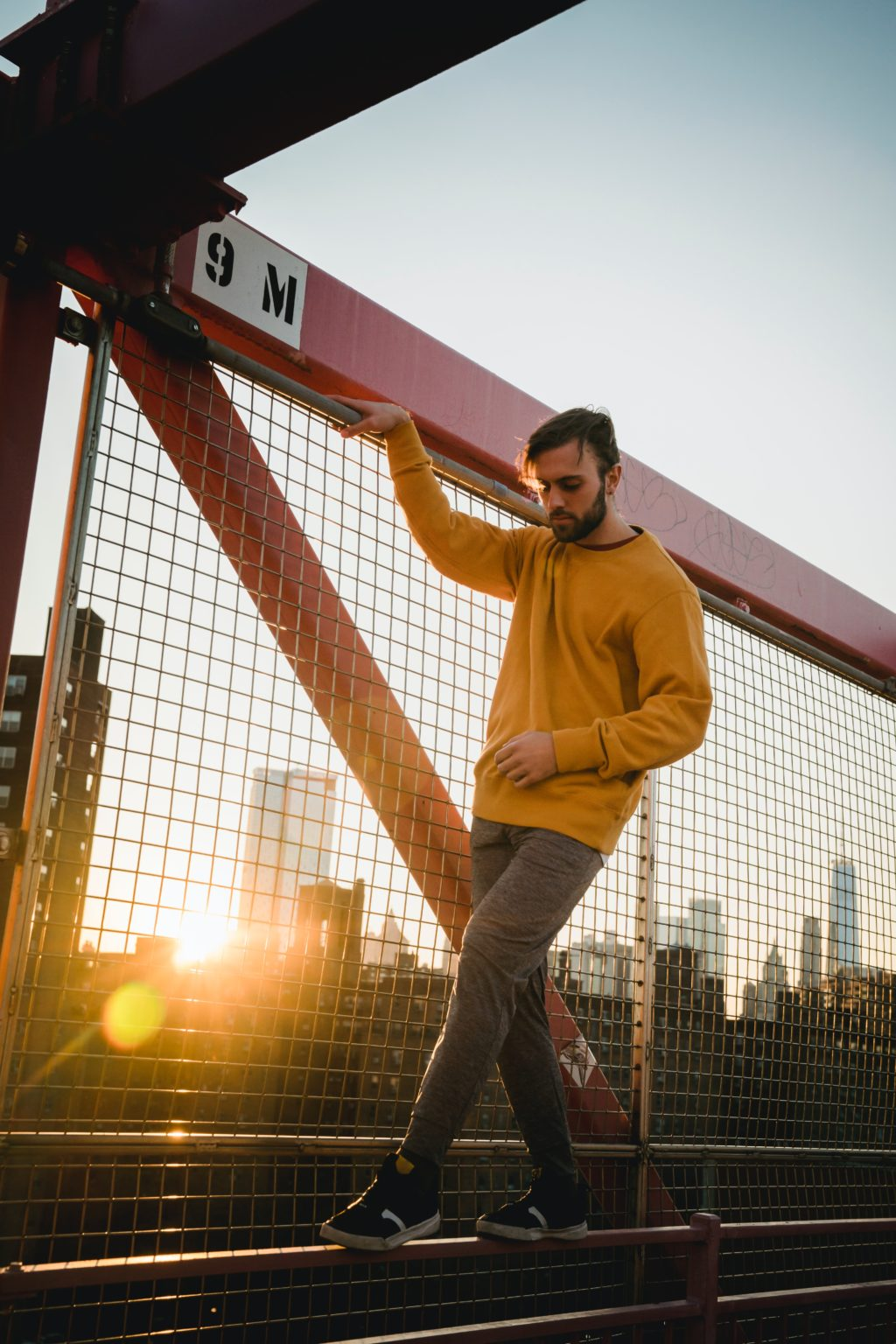 Portrait of man standing by fennce backlit by sun with lens flare.