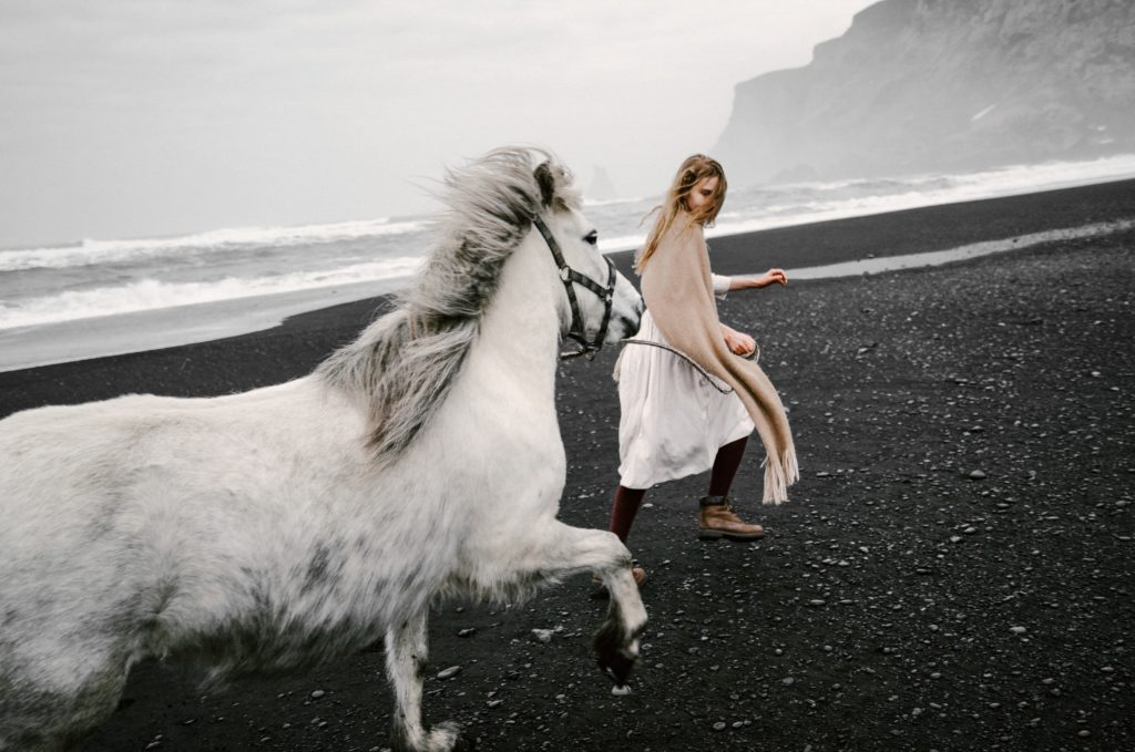 Young girl running on beach with beautiful white horse. Shot with Dutch Tilt.