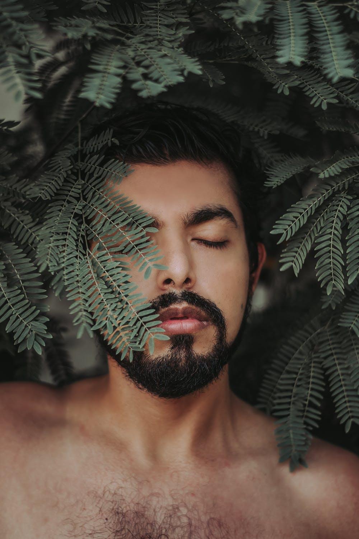 Bearded man behind leaf
