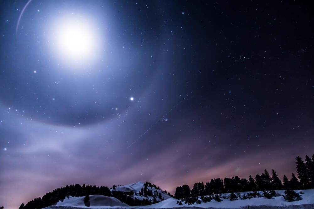 the moon, night sky, and stars with snowy landscape