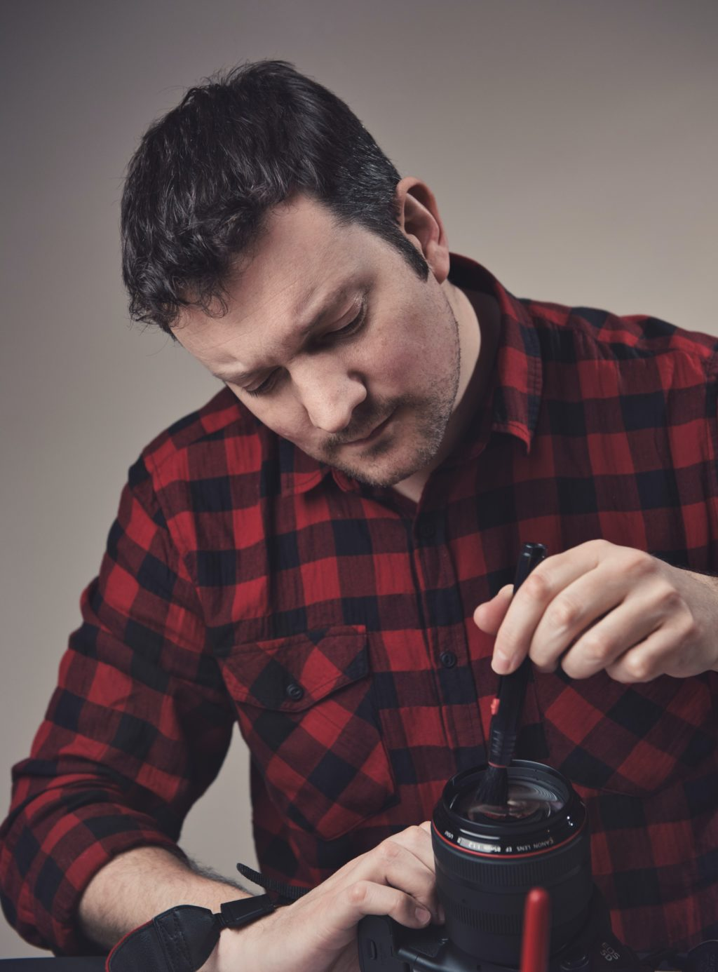 man cleaning camera lens.