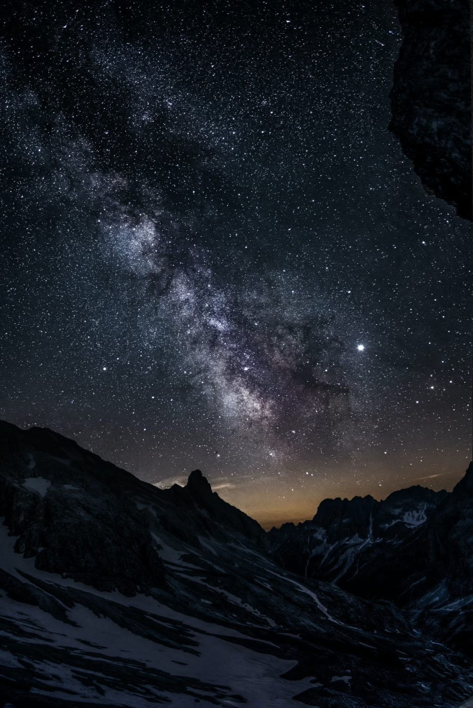 photo of mountain under starry night sky
