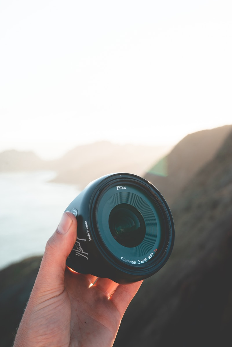 person holding camera lens shallow focus photography