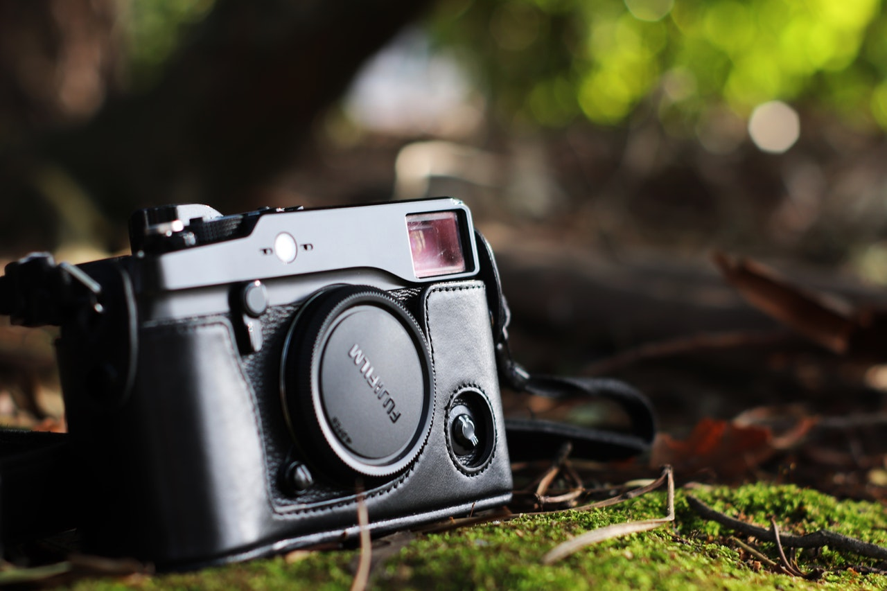 selective focus photo of black fujifilm camera on ground