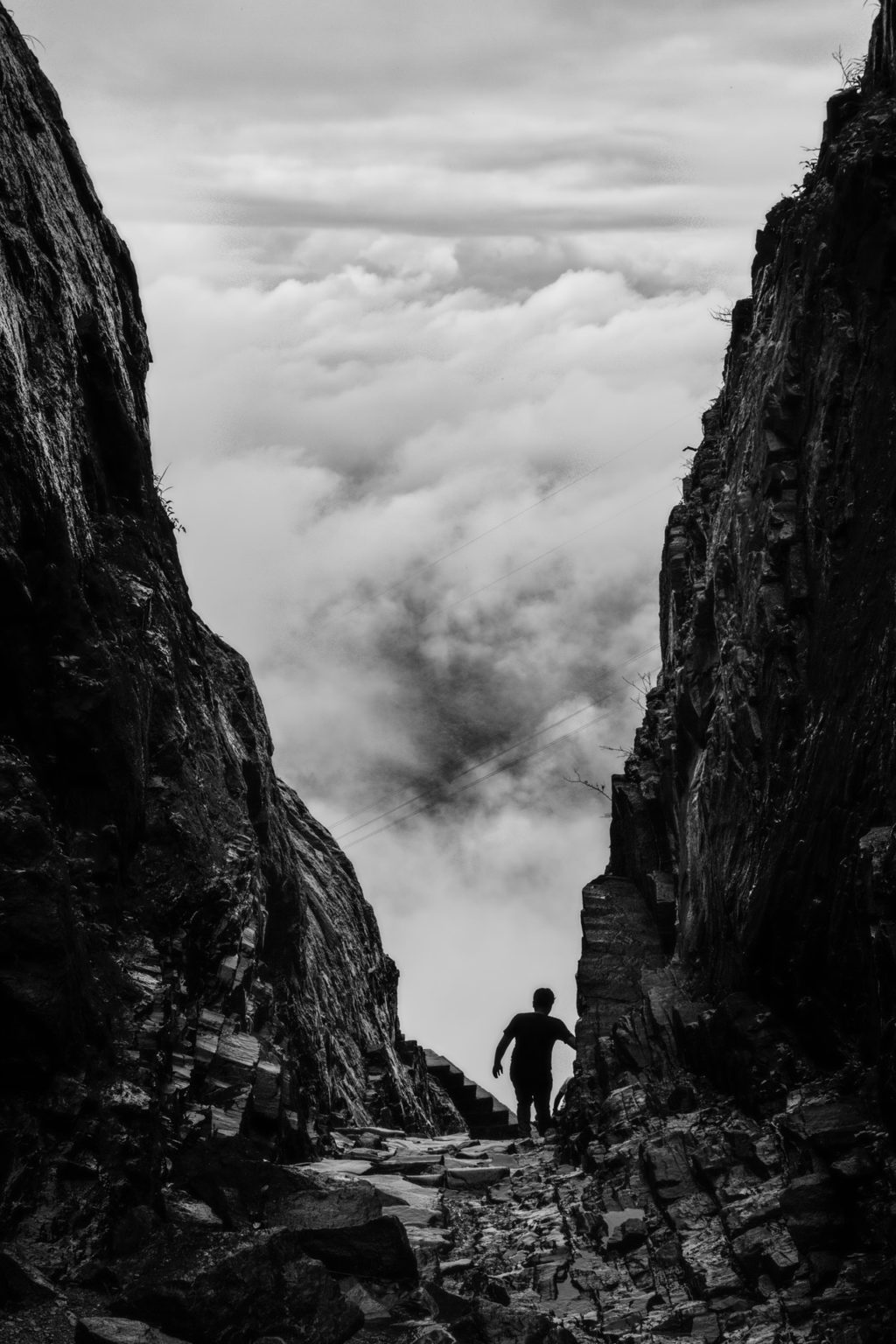 silhouette of man walking between two cliff