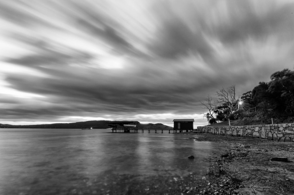 time lapse photo of a house near body of water in grayscale