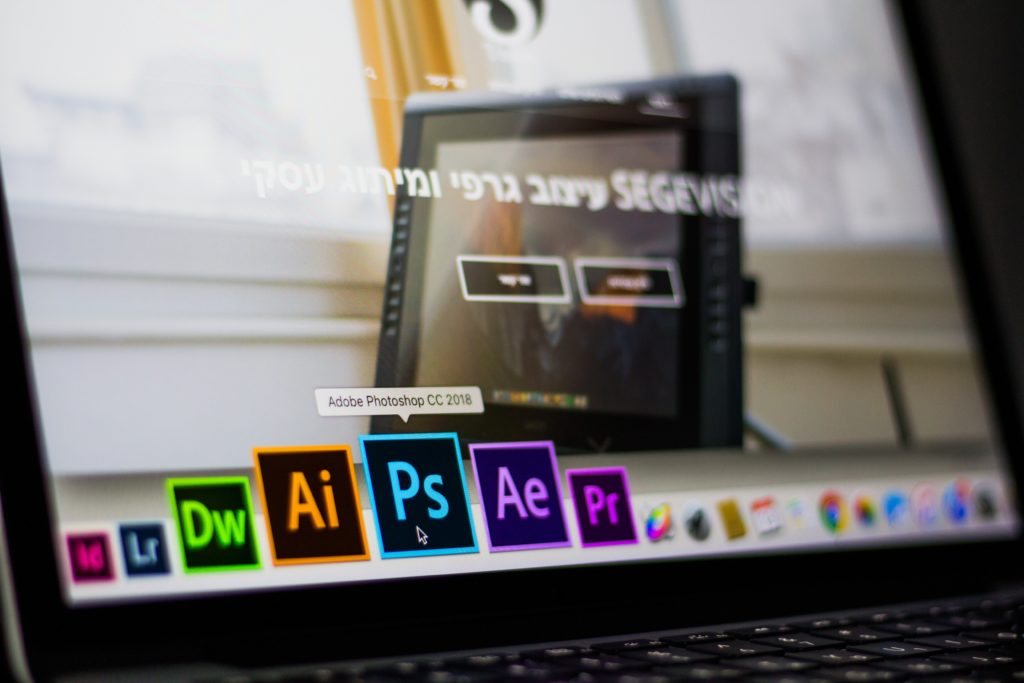 turned on laptop on desktop with hovered adobe photoshop cc
