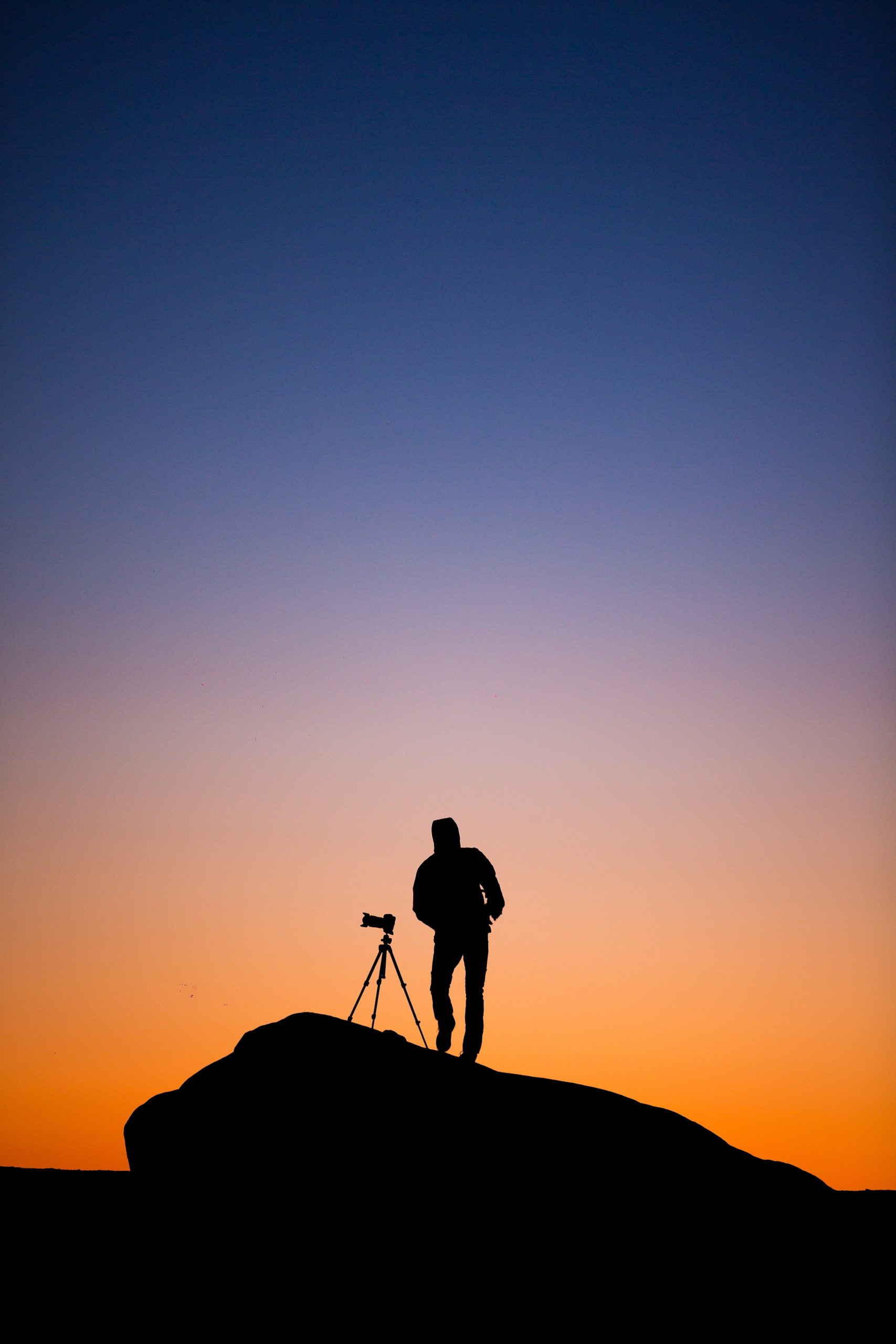 silhouette of person standing beside DSLR camera with stand at sunset
