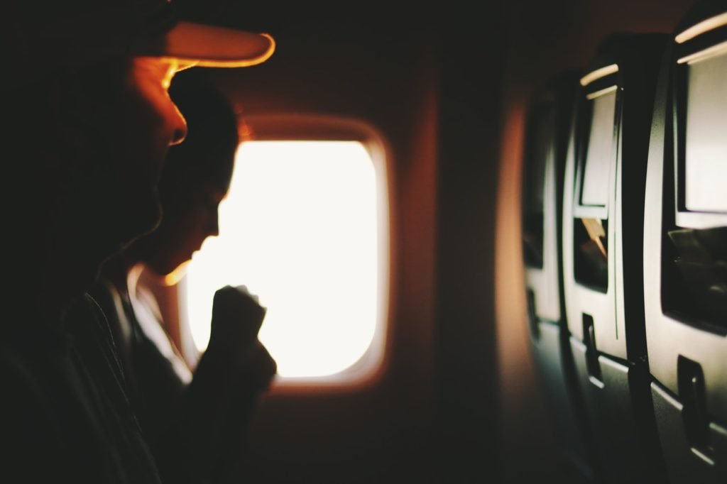two people sitting near window inside plane