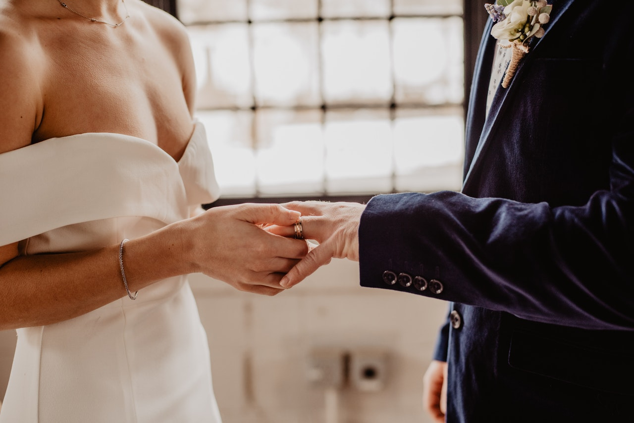 woman putting wedding ring on groom s finger